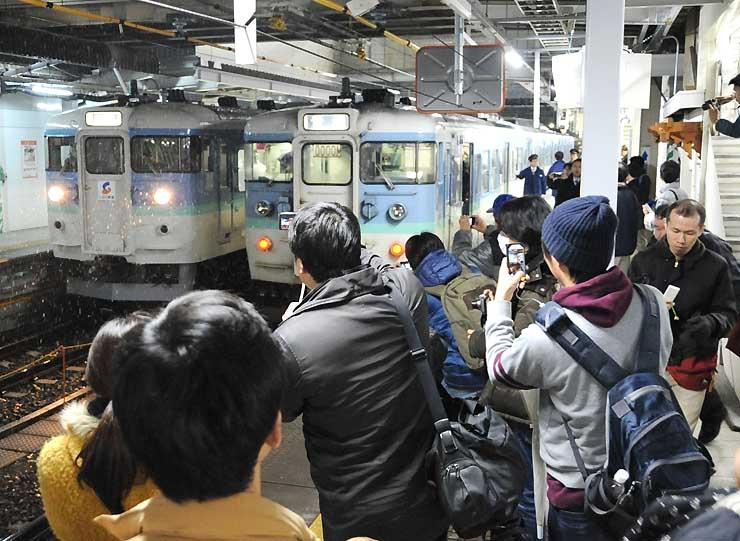 大勢の人たちに見送られて発車を待つ信越線の下り最終列車(右)=13日午後11時39分、JR長野駅