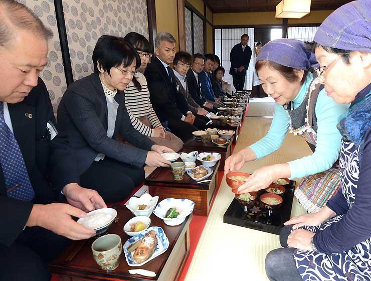 箱膳での食事体験で、真田邸で会員(右の2人)のもてなしを受ける参加者たち