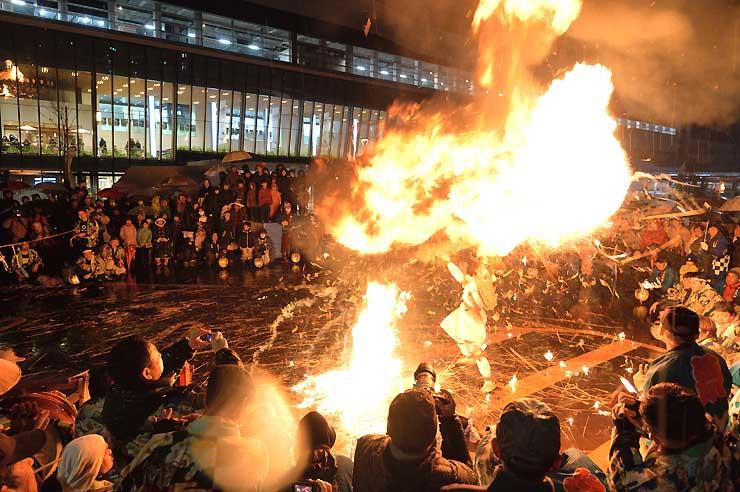 新幹線延伸開業の前夜祭で、炎のついたたいまつを回して舞う地元の伝統舞踊「奈良沢大天狗」=13日午後8時20分、飯山駅前