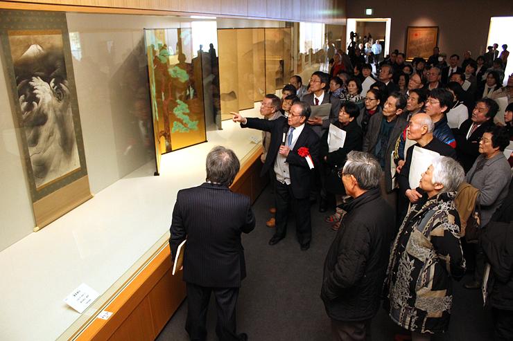 横山館長(左)の案内で富士山を描いた作品を鑑賞する来場者=県水墨美術館