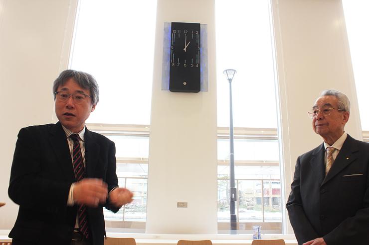 時計「時の融和」について説明する相川さん(左)。右は大黒副会長=北陸新幹線新高岡駅待合室
