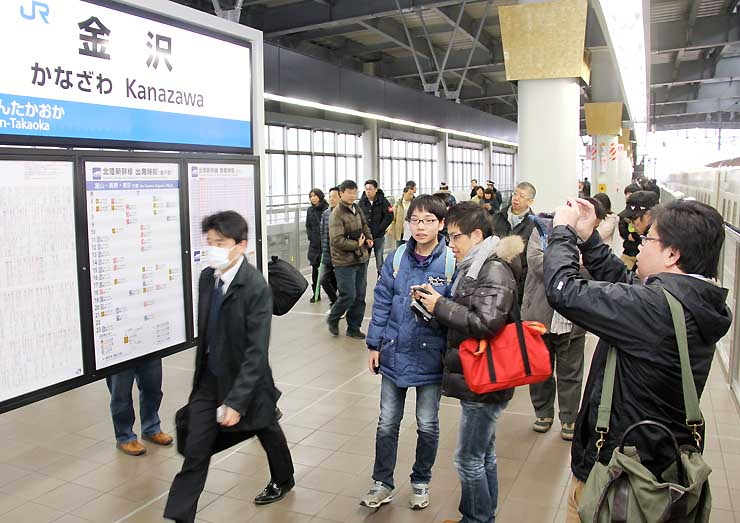 長野発の一番列車「はくたか591号」でJR金沢駅に到着し、「金沢」の駅名表示を撮影する人たち=14日午前7時39分