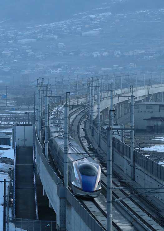 中野市内を金沢へ向けて走る北陸新幹線(長野経由)の長野発一番列車「はくたか591号」=14日午前6時18分