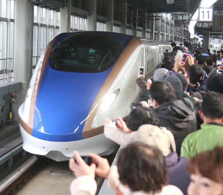 大勢の人に出迎えられ、金沢駅に到着した北陸新幹線の東京発一番列車「かがやき501号」=14日午前8時46分、JR金沢駅