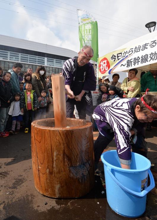 飯山駅の開業を祝い、駅前広場で行われた餅つき=14日午前11時15分