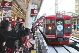 小旗を振ってしなの鉄道の列車を歓迎する市民ら=14日、妙高市