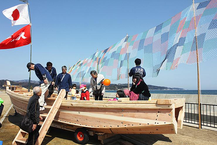 お披露目された木造和船に乗って楽しむ人たち。奥は「そらあみ」