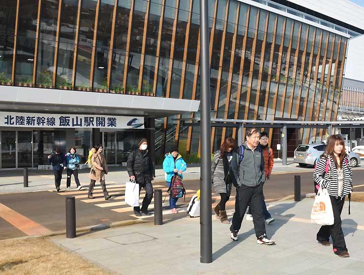 飯山駅からスノーシューのトレッキングツアーに向かう観光客ら