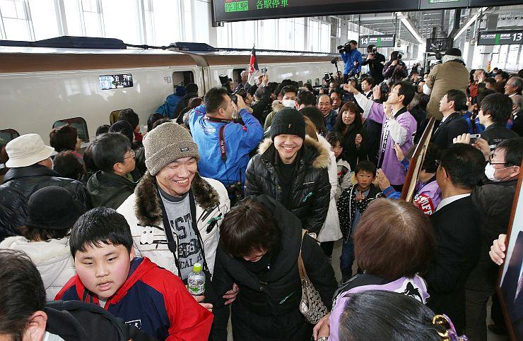 新幹線から降りた人と歓迎する住民らで混雑するホーム=14日午前10時30分すぎ、上越市の上越妙高駅