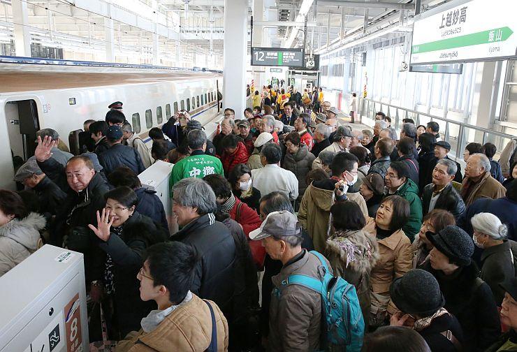 久しぶりの古里を楽しんだ後、帰りの新幹線に乗り込むツアー参加者=15日、上越妙高駅