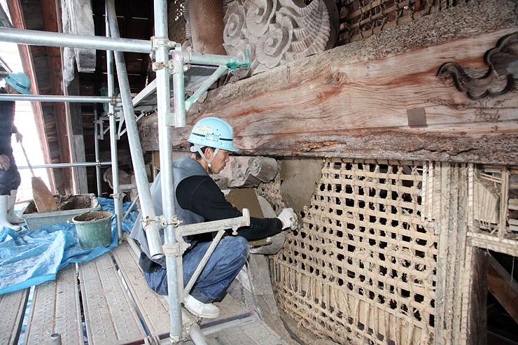 格子状に竹を組んだ小舞に、練り直した土を塗っていく左官職人=城端別院善徳寺
