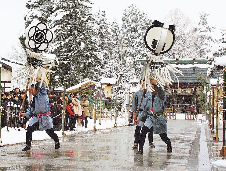 雪が降る中、勇ましいまとい振りを奉納する県若鳶会のメンバー=1月2日、射水神社