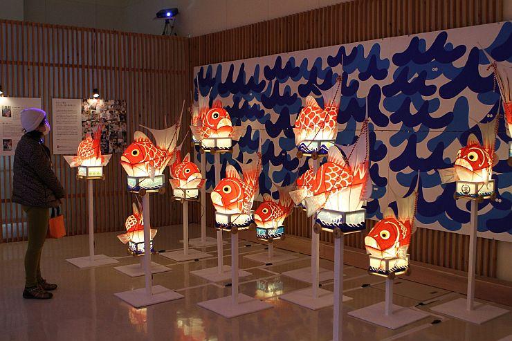 明かりをともした鯛車と荒波をイメージしたカラフルなイラストのコラボ企画展=新潟市西蒲区