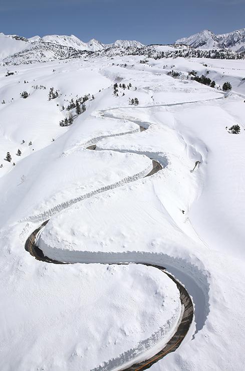 除雪が急ピッチで進み、雪原に曲線が刻まれた立山・七曲付近の高原バス道路=17日午前11時半ごろ、本社チャーターヘリから