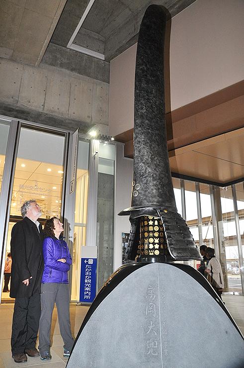 高さ4メートルの大兜を見上げるウッドさん夫妻=JR新高岡駅