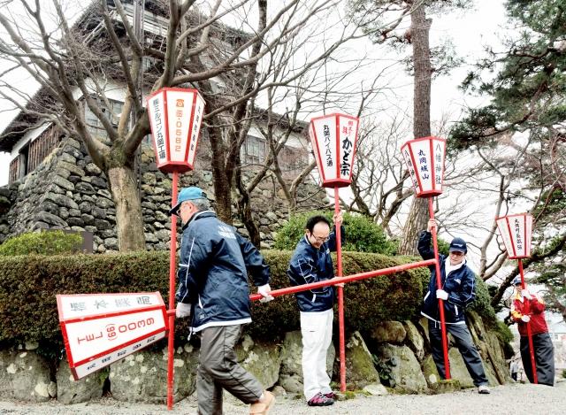 ぼんぼりを設置する観光協会員ら=20日、福井県坂井市の丸岡城