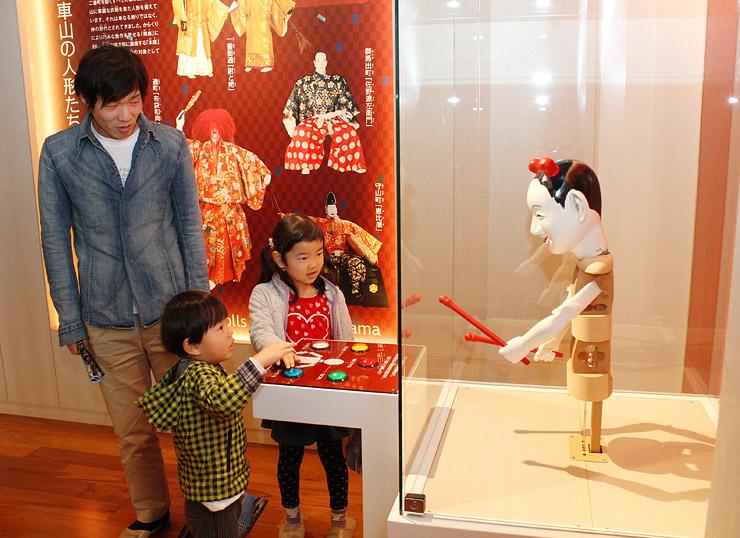 見学会でからくり人形の操作を体験する住民