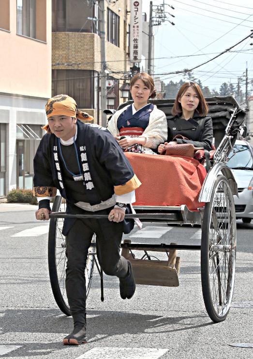 客を乗せて中心市街地を走る人力車=21日、飯田市