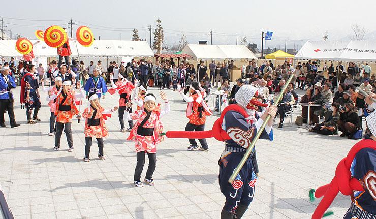 観客の前でにぎやかな舞を披露する栃屋獅子舞保存会=JR黒部宇奈月温泉駅前