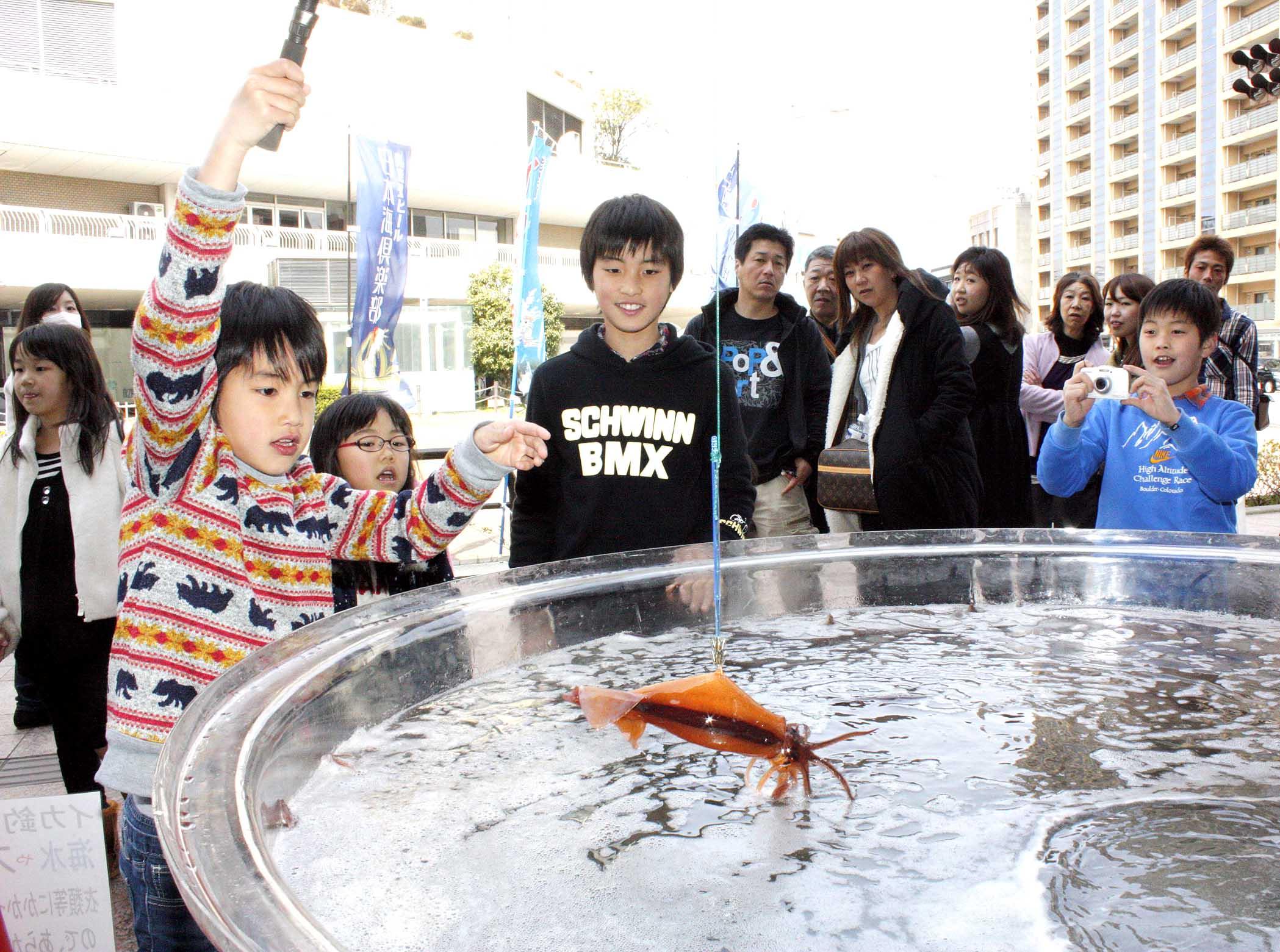 イカ釣りを楽しむ子ども=金沢市の近江町いちば館広場