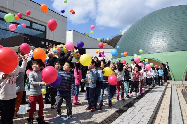 プラネタリウム施設(右)のリニューアルを祝い風船を飛ばす園児や関係者 新しくなったプラネタリウム施設で星空を楽しむ園児たち=23日、福井県敦賀市こどもの国
