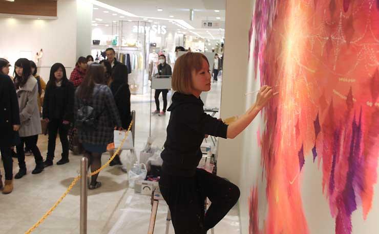 JR長野駅の駅ビル「MIDORI長野」の3階で壁画制作に取り組む越さん