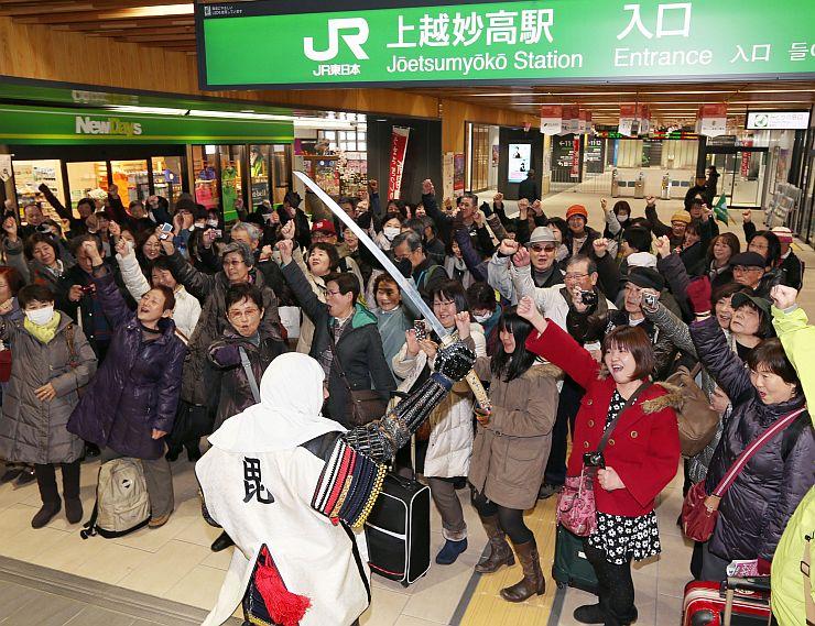 おもてなし武将隊らの歓迎を受け、勝ちどきを上げるツアー客=24日、上越市の上越妙高駅