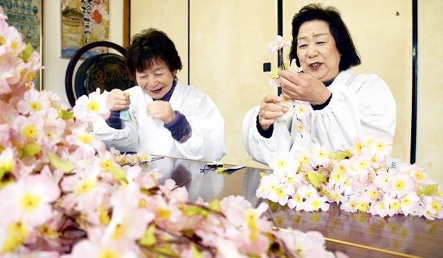 心を込めて桜の小枝に短冊や絵馬をつける金ケ崎町婦人部メンバー=25日、福井県敦賀市の金崎宮
