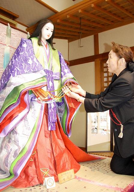 紫式部人形と、新しい十二単を製作した三田村さん=越前市の藤波亭
