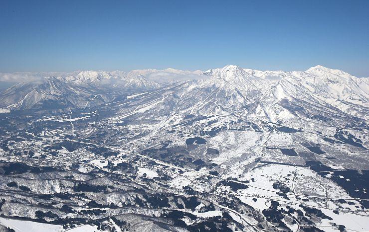 妙高戸隠連山国立公園では妙高山をはじめ美しい山々が連なる。白い山肌と青空とのコントラストが映えた=26日、本社ヘリから