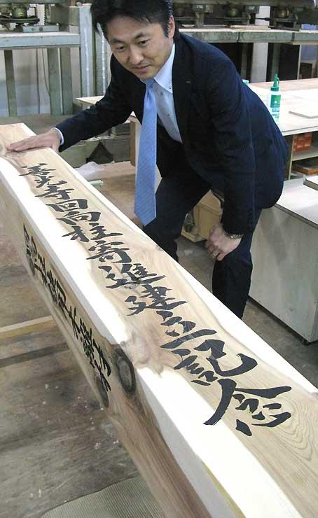 筆文字が印字され、銀座でのお披露目を待つミニ回向柱=27日、長野市