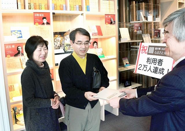 柿木館長(右)から記念品を贈られる上禰さん夫婦=28日、福井市の福井県ふるさと文学館