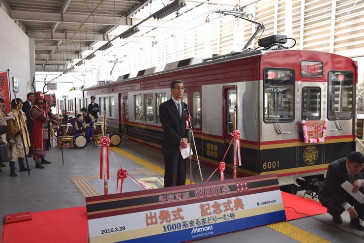 新型車両「6000系」の隣であいさつする角田社長=28日、別所線上田駅
