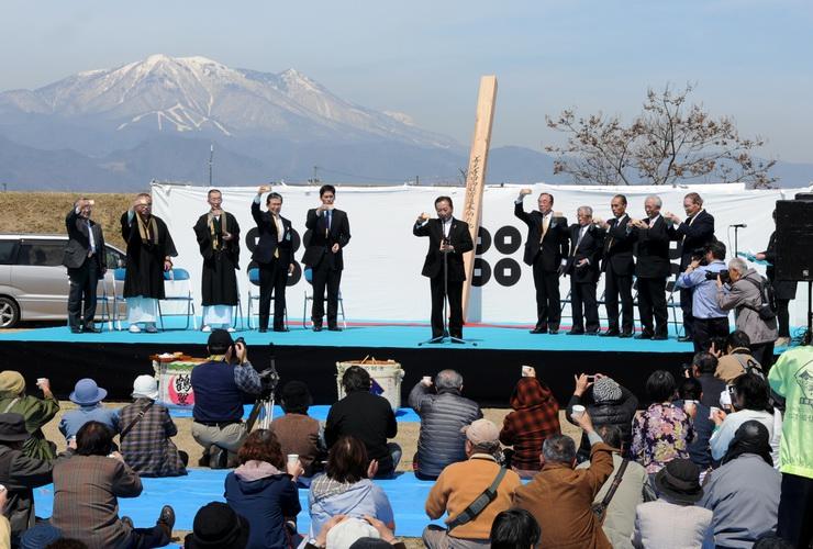 披露されたミニ回向柱(舞台中央)の前で乾杯する参加者