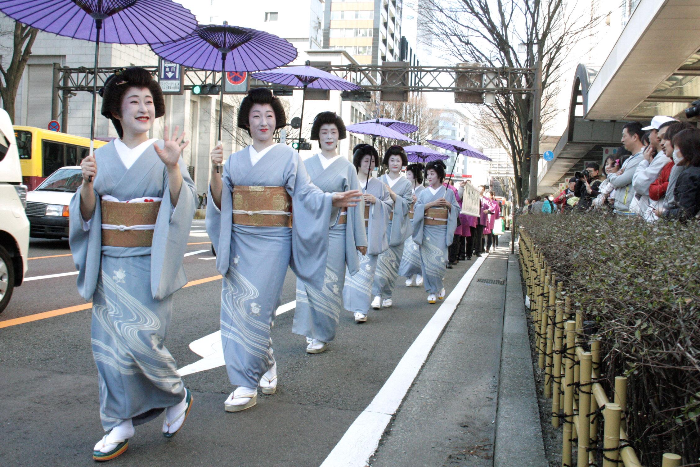 新幹線開業と再開発事業の上棟を祝い歩く芸妓=香林坊大和前