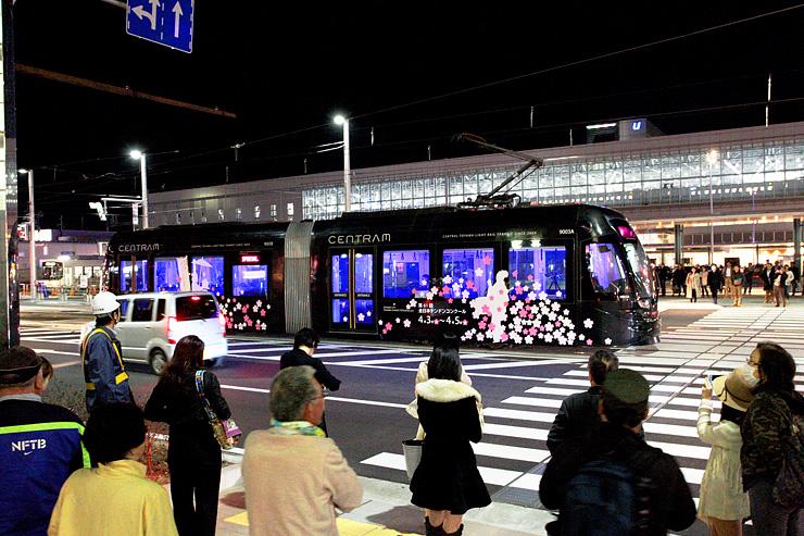 鮮やかな光を放ちながら走る「ライトラム」。大勢の通行人が見入っていた=JR富山駅前
