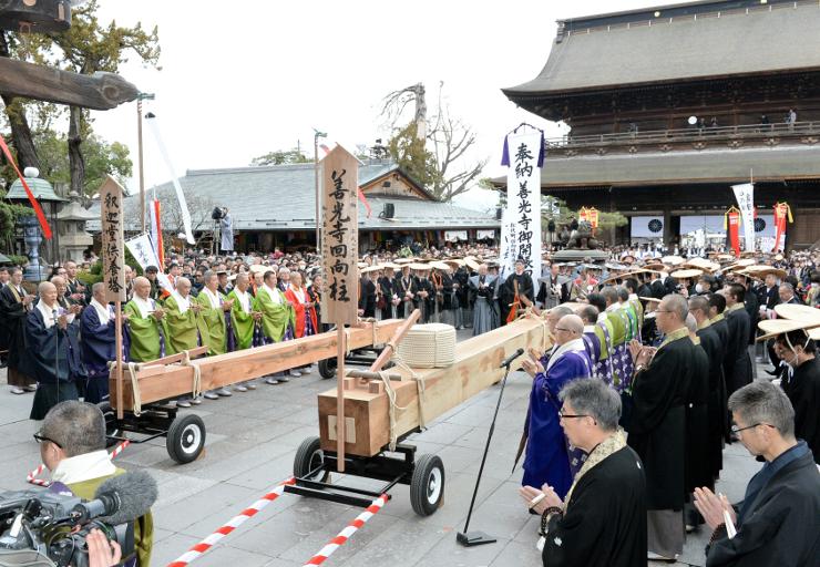 本堂前に到着した回向柱を囲んで行われた受け入れ式=29日午後2時34分、長野市の善光寺