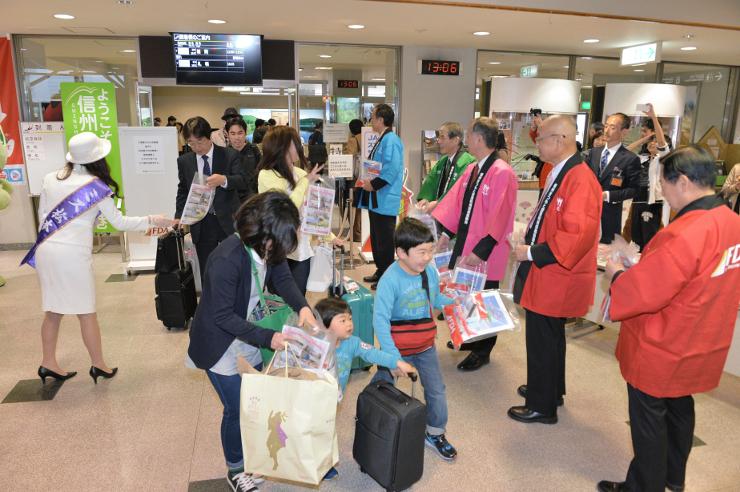 県営松本空港に降り立ち、歓迎を受ける福岡線の利用者ら=29日午後1時6分、松本市