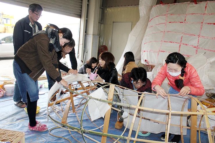 「文久の大行燈」の骨組みに和紙を貼る参加者ら=福野西部地区防雪センター