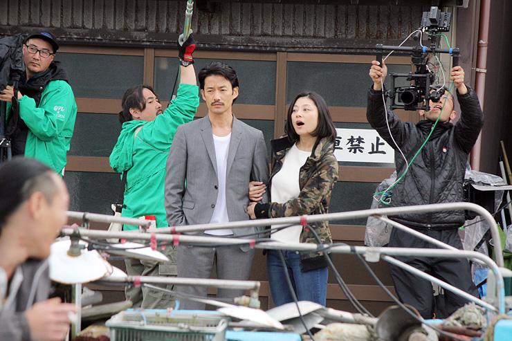 内川沿いの散策シーンの撮影に臨む竹野内豊さん(中央左)と小池栄子さん(同右)=射水市内