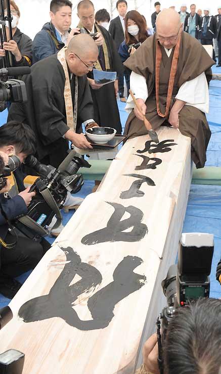 空、風、火、水、地などを意味する梵字を回向柱に書き入れる大勧進の小松玄澄貫主=1日午前11時8分、長野市の善光寺