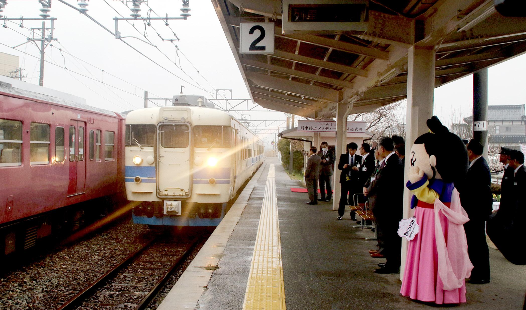 「ハナミズキ」の音楽とともに列車を迎える関係者=1日午前10時、中能登町のJR良川駅