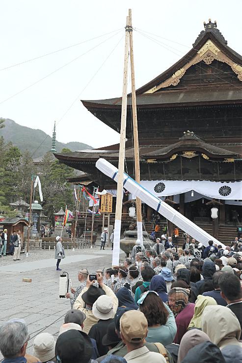 木遣り歌が流れる中、厳かに建立される回向柱=3日午後1時27分、長野市の善光寺本堂前