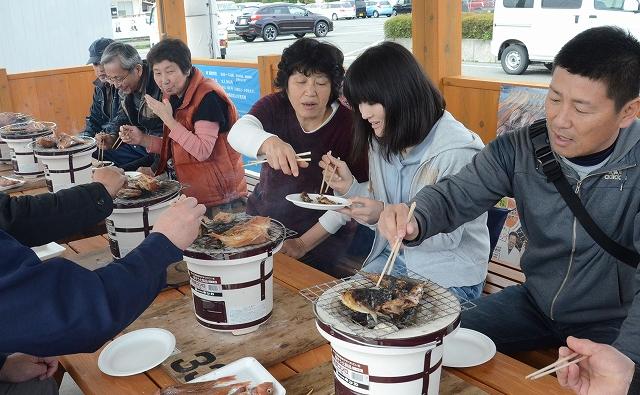 焼き立てのサバやアジのしょうゆ干しを堪能する観光客ら=4日、福井県小浜市川崎2丁目