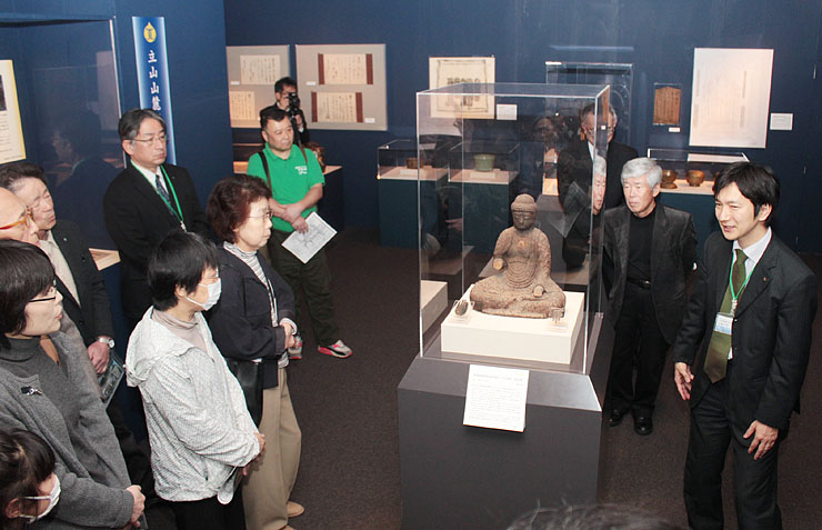 国内で3番目に古い鉄製仏像と分かった鉄造阿弥陀如来坐像に見入る来場者=立山博物館
