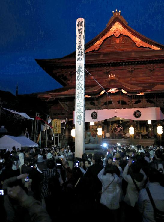 開眼法要を終え、ライトアップされた回向柱と善光寺本堂。回向柱の下には、参拝者のカメラの明かりが広がった=4日午後6時37分、長野市