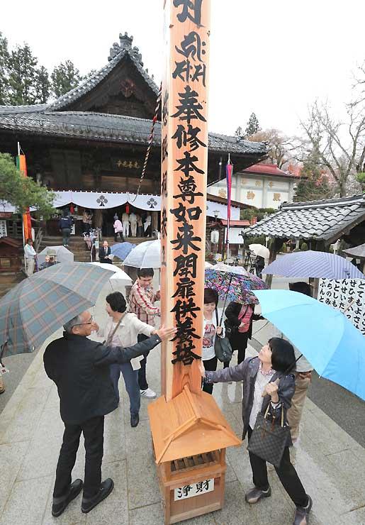 雨の中、前立本尊と「善の綱」で結ばれた回向柱に触れる参拝者=5日、飯田市の元善光寺
