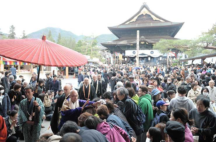 御開帳初日、大勢の参拝者が訪れた善光寺。小松貫主(傘の下、紫の衣)が参拝者の頭に数珠を当てる「お数珠頂戴(ちょうだい)」には長い列ができた=5日午前10時32分