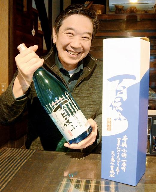 「雲城水」を使った日本酒「百伝ふ」を持つ上田会長=6日、福井県小浜市一番町
