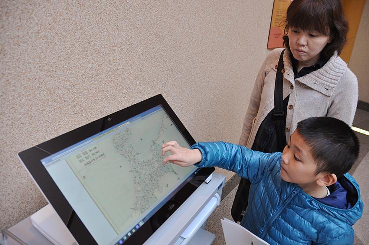 「加越能三州郡分略絵図」など公開された信由の史料を閲覧する親子連れ